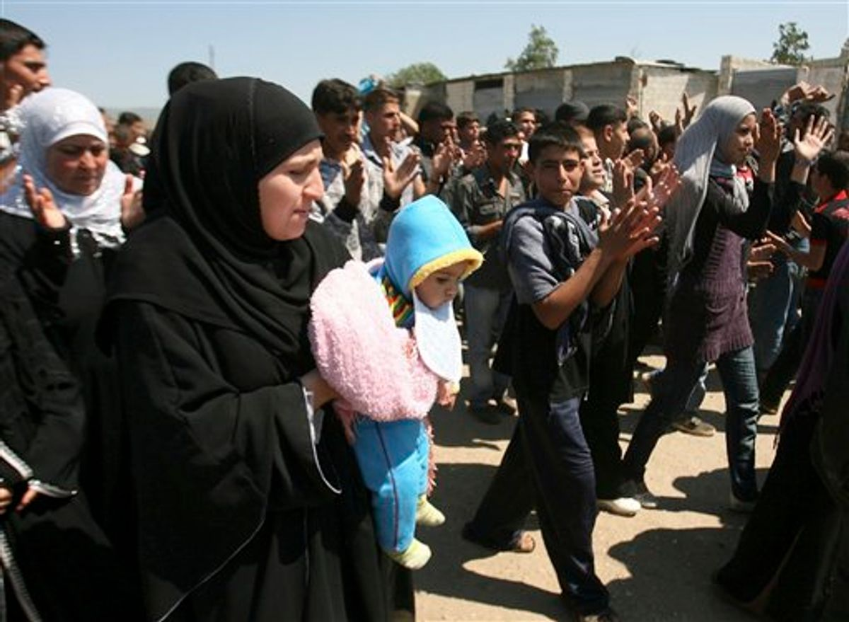 """Syrian citizens who fled from violence from the western Syrian villages along the Lebanese-Syrian border, protest as they shout slogans against Bashar Assad and his regime, in the Wadi Khaled area, about one kilometer (0.6 miles) from the Lebanon-Syria border, north Lebanon, on Monday May 16, 2011. Carrying mattresses and bags of clothing, Syrians fleeing their homeland described a """"catastrophic"""" scene Monday in a besieged border town that has been largely sealed off as the army tries to crush a two-month uprising. (AP Photo) (AP)"""