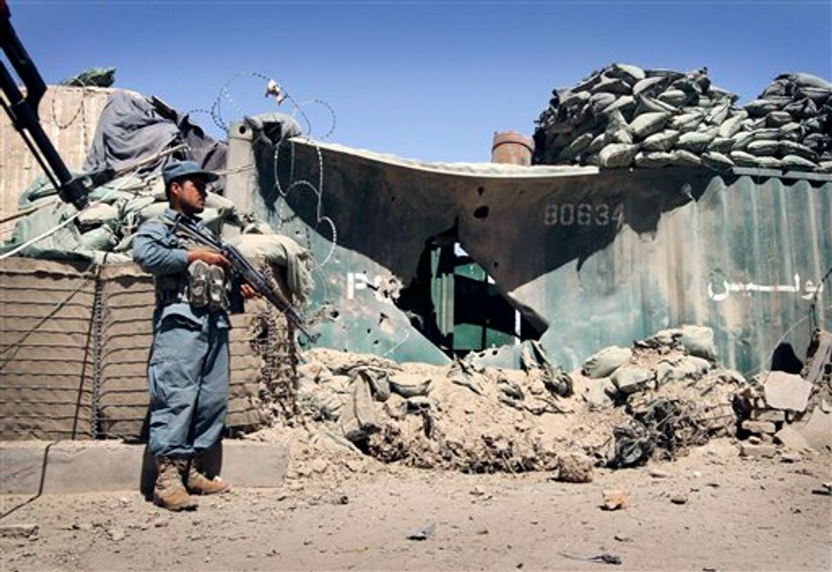 An Afghan policeman stands guard at the scene of an explosion in Kandahar south of Kabul, Afghanistan on Sunday, May 22, 2011. In Kandahar, two police officers suffered injuries Sunday when a motorcycle laden with explosives detonated as they tried to disarm it, the ministry said. (AP Photo/Allauddin Khan) (AP)