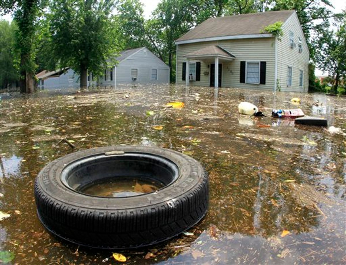 Trash floats by flooded homes on Monday, May 9, 2011, in Memphis, Tenn. The swollen Mississippi River could crest as early as Monday night. (AP Photo/Mark Humphrey) (AP)