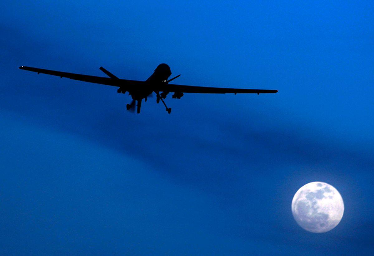 A U.S. Predator drone flies over the moon above Kandahar Air Field, southern Afghanistan.