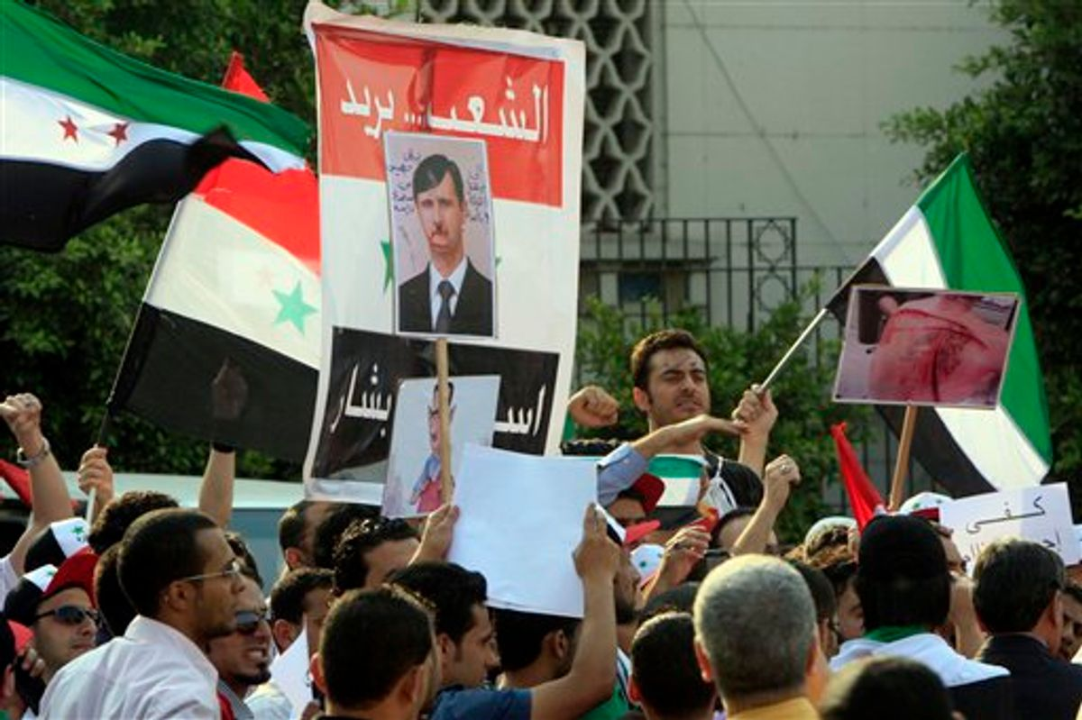 """Syrian protesters chant slogans and hold anti-Syrian President posters during a demonstration demanding that Syria's President Bashar Assad step down, in front of the Arab League headquarters building in Cairo, Egypt, Sunday, May 15, 2011. Hundreds of Syrians fled to neighboring Lebanon to escape a violent crackdown against an anti-government uprising that has claimed the lives of more than 800 civilians, Lebanese security officials and a leading human rights group said. Arabic read """" people want Assad step down"""".  (AP Photo/Amr Nabil) (AP)"""
