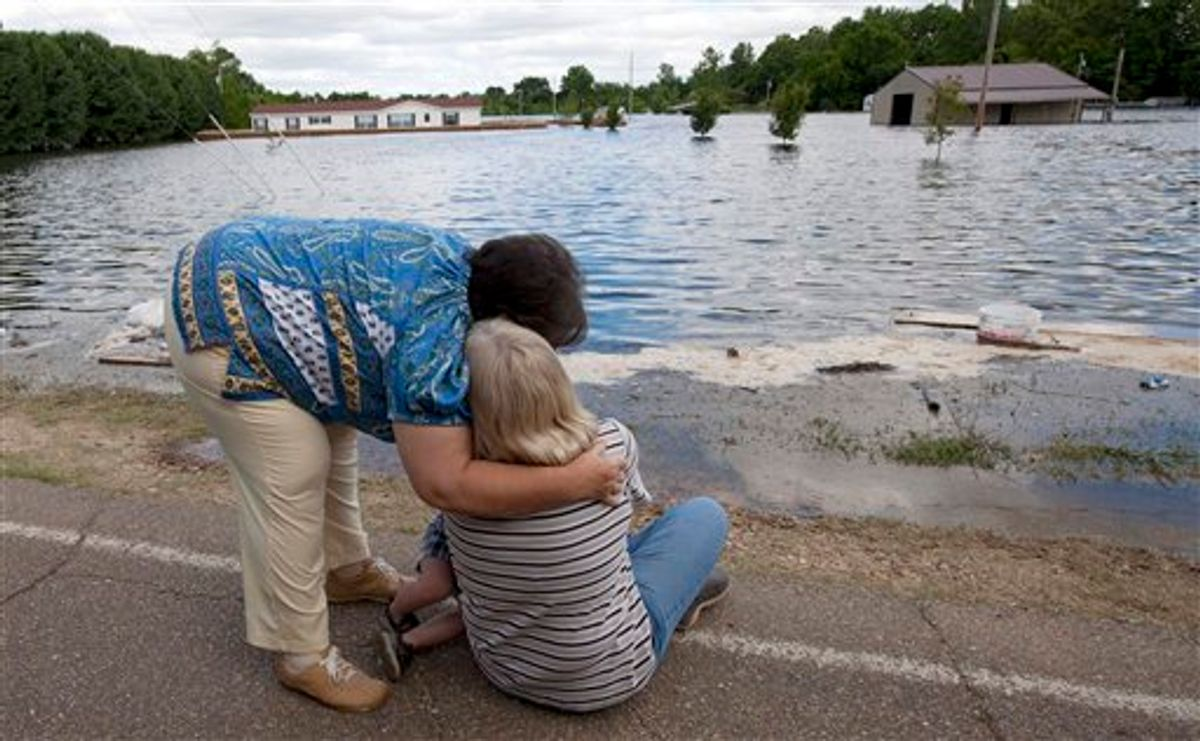"""Brenda Hynum, left,  hugs her daughter Debra Emery as she watches floodwaters rise around her mobile home in Vicksburg, Miss., Monday, May 16, 2011. A sand berm they built around their trailer failed in the night and floodwaters from the rising Mississippi river rushed in. """"We tried so hard to stop it. It goes from anger to utter disbelief that this could happen. I just want to go home."""" Emery said. (AP Photo/Dave Martin)  (AP)"""