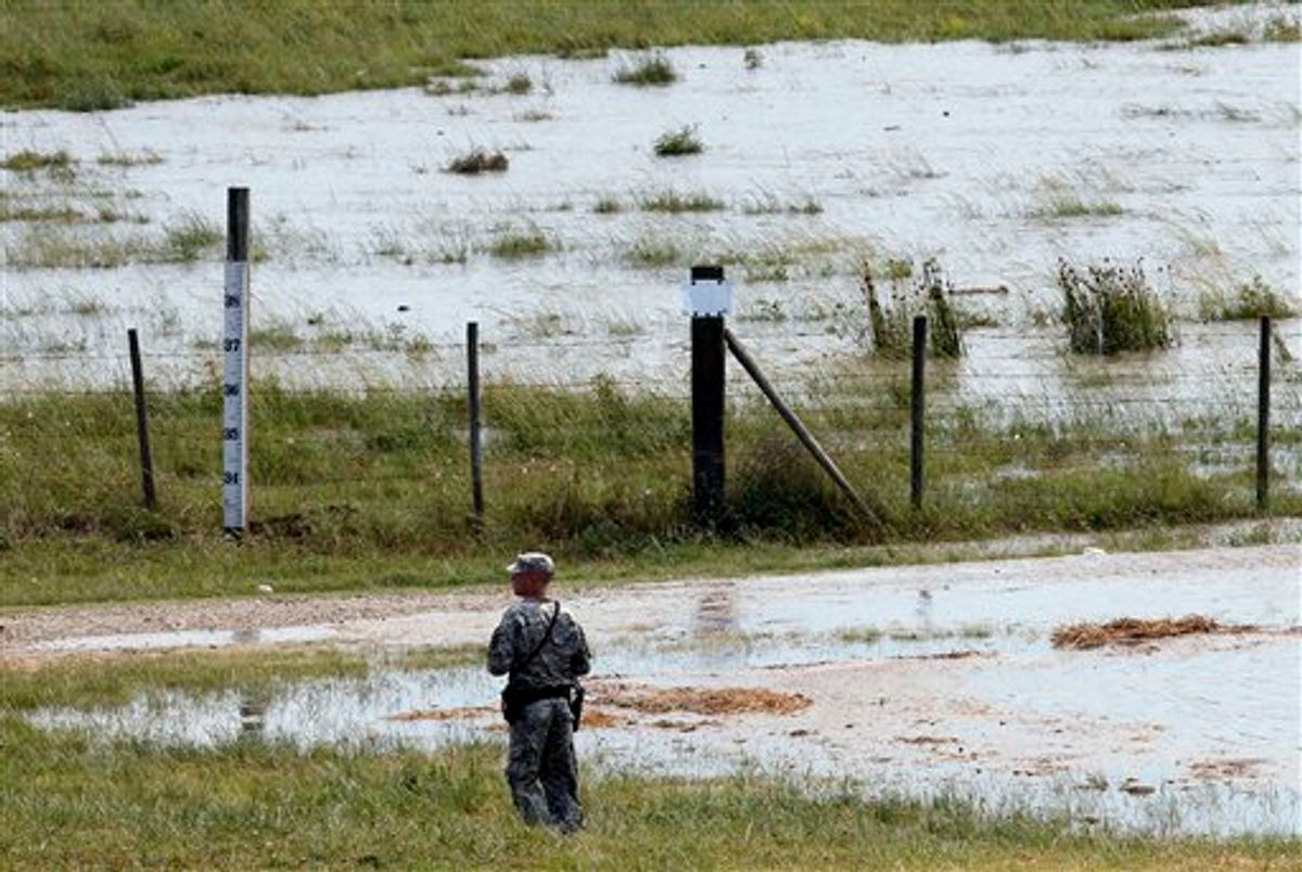 A member of the Louisiana National Guard stands guard as water diverted from the Mississippi River through a bay in the Morganza Spillway begins to fill a pasture in Morganza, La., Saturday, May 14, 2011.   Opening the Morganza spillway diverts water away from Baton Rouge and New Orleans, and the numerous oil refineries and chemical plants along the lower reaches of the Mississippi. (AP Photo/Patrick Semansky)  (AP)