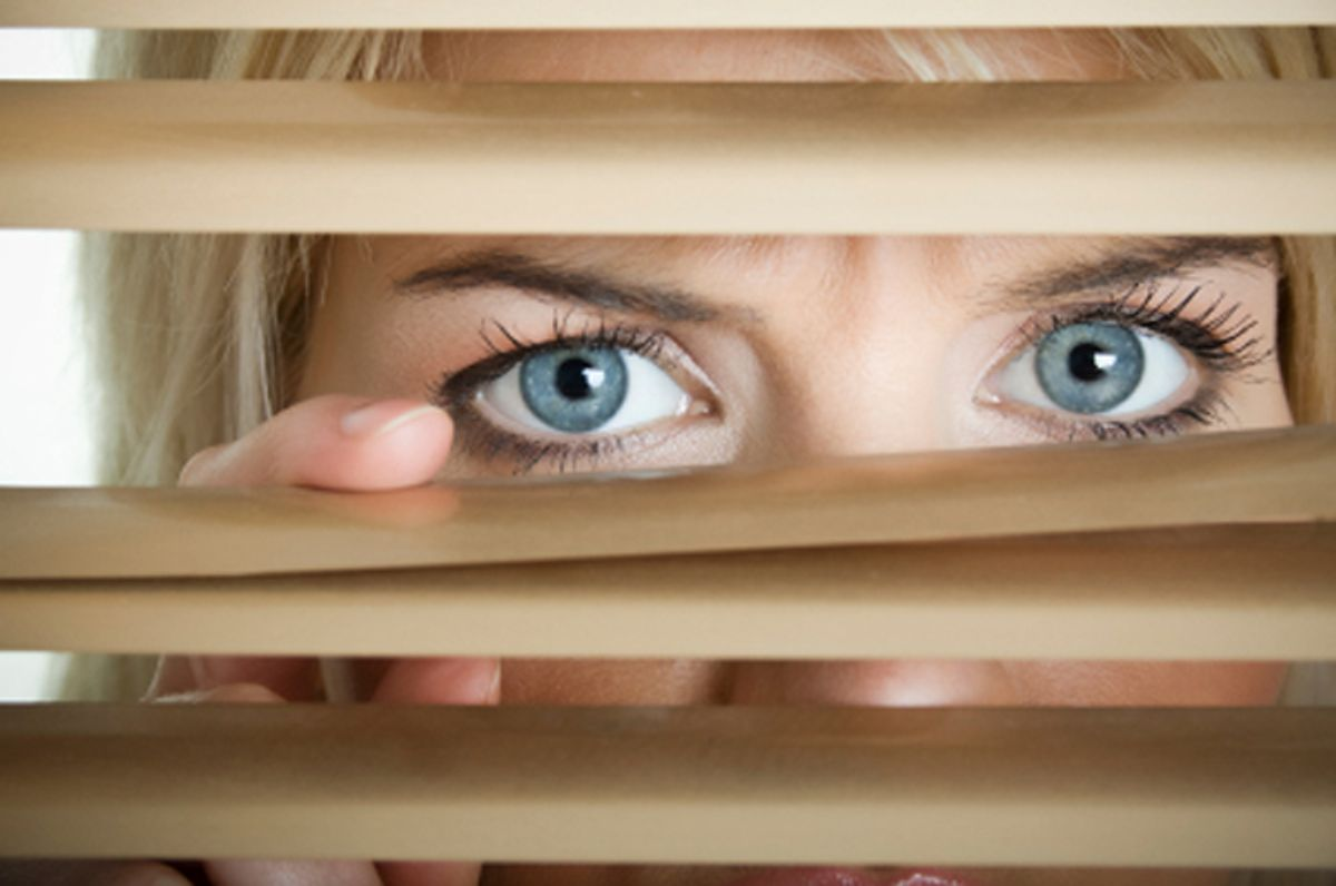 Young scarry women looking through window blinds