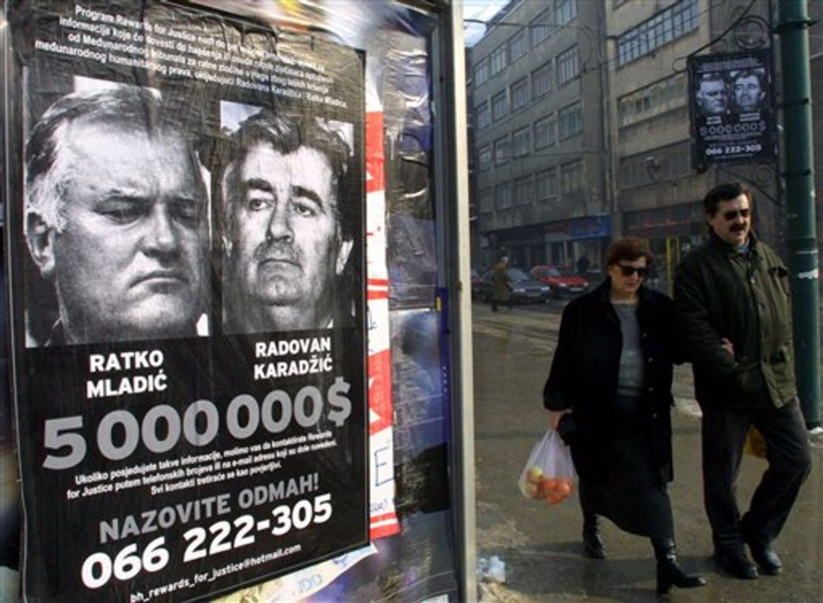 FILE In this Jan. 20, 2002 photo, a Bosnian couple passes by a poster of  Bosnia's two most wanted war crimes suspects, the leader of Bosnian Serbs Radovan Karadzic and his war time commander Gen. Ratko Mladic, in Sarajevo.  Mladic, Europe's most wanted war crimes fugitive, has been arrested in Serbia, the country's president said Thursday, May 26, 2011. Mladic has been on the run since 1995 when he was indicted by the U.N. war crimes tribunal in The Hague, Netherlands, for genocide in the slaughter of some 8,000 Bosnian Muslims in Srebrenica and other crimes committed by his troops during Bosnia's 1992-95 war.  (AP Photo/Sava Radovanovic) (AP)