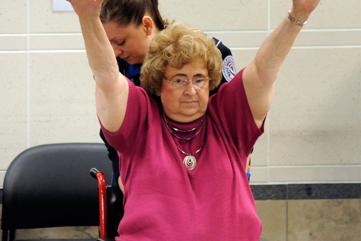 A TSA officer searches a traveler in a wheelchair at the Minneapolis-St. Paul International Airport.