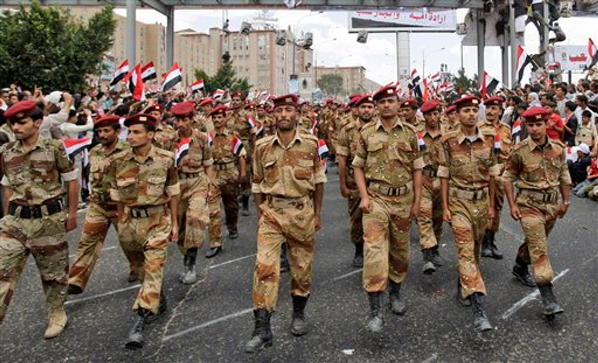 Yemeni army soldiers who joined the anti-government protestors , march during a ceremony to commemorate the anniversary of Yemen's reunification, in Sanaa, Yemen, Sunday, May 22, 2011. A deal for Yemeni leader Ali Abdullah Saleh to step down after 32 years in power was thrown into doubt Sunday after the ruling regime brought hundreds of loyalists into the streets to protest the pact and said he would not sign unless a public ceremony were held that included opposition leaders. (AP Photo/Hani Mohammed) (AP)