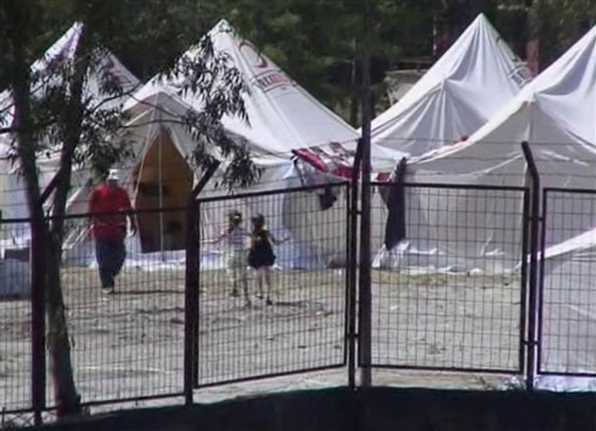 This image taken from video released by Anatolia Agency shows two Syrian refugee children playing outside tents in a camp built to accommodate 5,000 people in the town of Yayladagi, Hatay province, Turkey near the Syrian border Thursday June 9, 2011. About 1,000 Syrians fleeing violence crossed into Turkey overnight, raising the total number of refugees in the country to 1,600. Hundreds of Syrians fled to Turkey on Thursday as elite Syrian troops moved to encircle a restive town ahead of a possible assault, sharply escalating the upheaval that threatens the 40-year regime led by President Bashar Assad.   (AP Photo/Anatolia Agency via APTN) TURKEY OUT, TV OUT (AP)