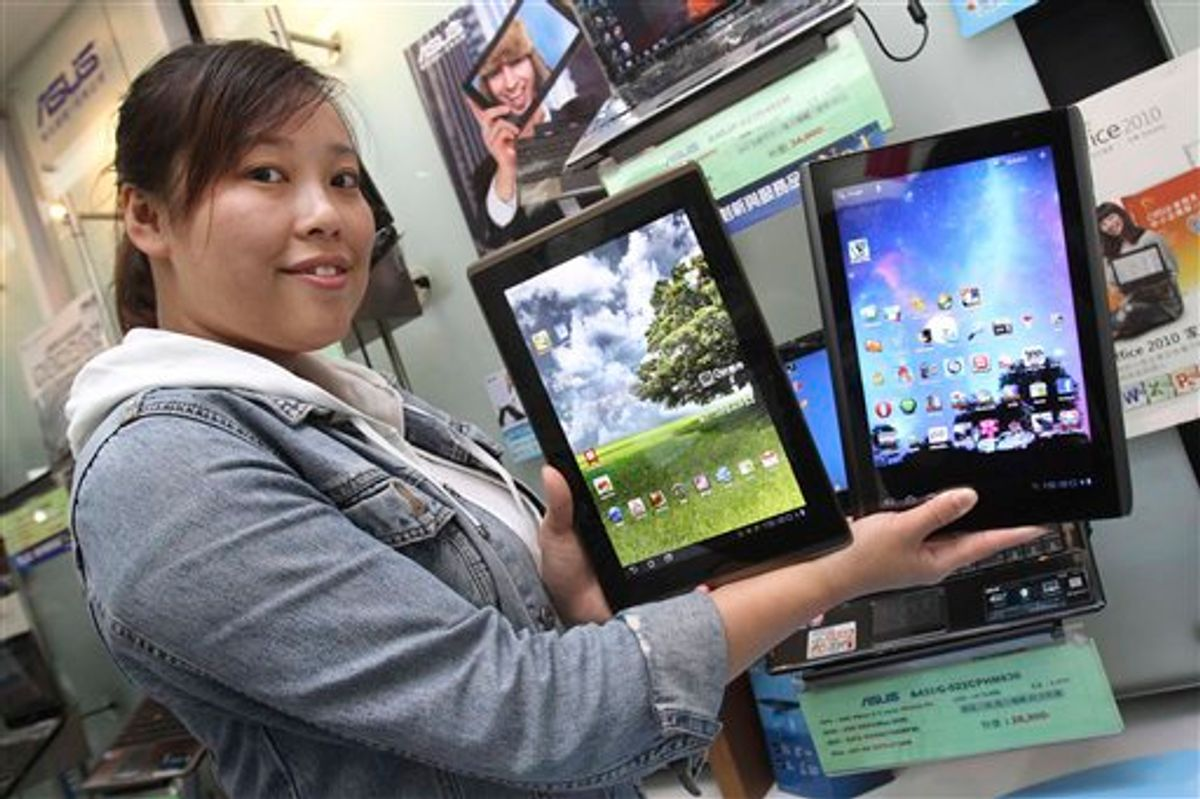 A showroom employee displays tablet computers from Taiwan's top two PC vendors, Acer Inc. and AsusTek Computer Inc. in Taipei, Taiwan, Saturday, May 28, 2011. Dozens of global computer firms and their obsession to get a piece of the expanding tablet computing market will be on full display Tuesday  May 31, 2011, as Computex, the world's second largest computer show, begins its annual five-day run in Taipei. (AP Photo/Chiang Ying-ying) (AP)