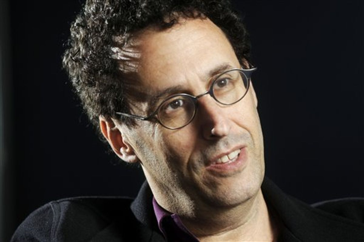 """FILE - In this April 30, 2009 photo, Tony Kushner is shown during a break from rehearsal of his new play at the Guthrie Theatre in Minneapolis, Minn.,  Kushner won a Pulitzer Prize for """"Angels in America,"""" his epic play about the AIDS epidemic, and is a New York literary fixture who has received more than a dozen honorary degrees from American colleges and universities.  So it was a shock when the Board of Trustees of the City University of New York voted last month to withhold a promised honorary degree after a trustee said the playwright was anti-Israel. CUNY later backtracked under a barrage of criticism, and Kushner will accept his degree on Friday, June 2, 2011. (AP Photo/Craig Lassig)  (AP)"""