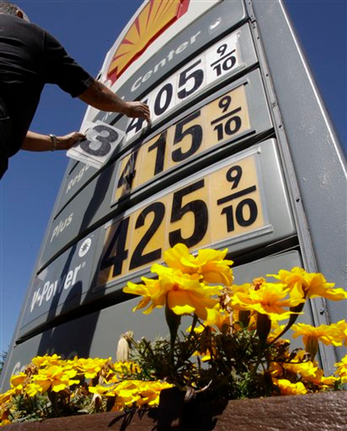 In this June 21, 2011, photo, Shell gas worker Toke Fusi lowers gas prices at a Shell gas station in Menlo Park, Calif. (AP Photo/Paul Sakuma)