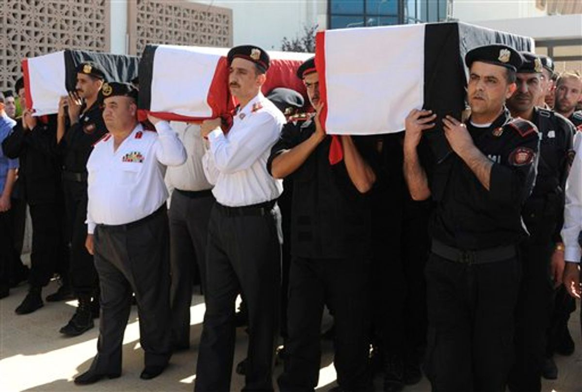 In this photo released by the Syrian official news agency SANA and according to them, Syrian policemen carry the coffins of their comrades who were killed in recent violence in the country, during their funeral procession at the Police Hospital in Damascus, Syria on Tuesday, June 7, 2011. Residents fled the northern region of Jisr al-Shughour on Tuesday where authorities said weekend clashes between armed men and government troops killed 120 security forces, fearing retaliation from a regime known for ruthlessly crushing dissent. (AP Photo/SANA) EDITORIAL USE ONLY (AP)