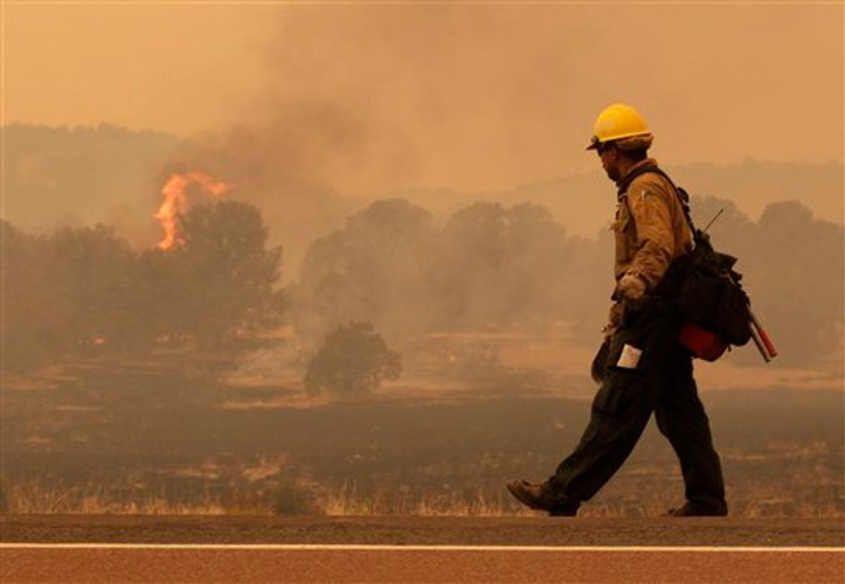 Firefighter Rigoberto Torres, of Orange Cove, Calif., walks along the road while watching a flame during the Wallow fire in the Apache-Sitgreaves National Forest near Springerville, Ariz., Tuesday, June 7, 2011. Officials say the blaze has already burned 486 square miles and winds have been driving the flames 5 to 8 miles a day since the fire began a week ago. (AP Photo/Jae C. Hong)  (AP)