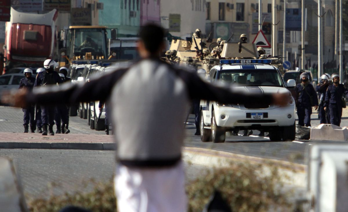 A resident spreads his arms in front of riot police and tanks moving into the Shiite Muslim village of Malkiya, Bahrain, southwest of Manama, on Sunday, March 20, 2011.Bahraini authorities are trying to crush a revolt by the nation's majority Shiites for greater political freedoms. Saudi Arabia and other Gulf states have sent forces to help Bahrain's Sunni dynasty. (AP Photo/Hasan Jamali) (Associated Press)