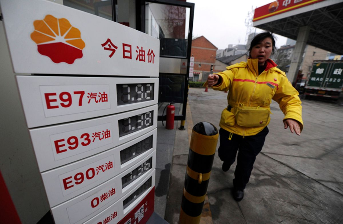 An employee gestures to stop a photographer from taking pictures near a board showing recently increased fuel prices at a gas station in Hefei, Anhui province April 7, 2011. China will increase retail gasoline and diesel prices by 5-5.5 percent to new record highs from Thursday, the government said, easing the burden of state refiners who face international oil prices at 2.5-year highs. REUTERS/Stringer (CHINA - Tags: BUSINESS ENERGY)  (© Jianan Yu / Reuters)