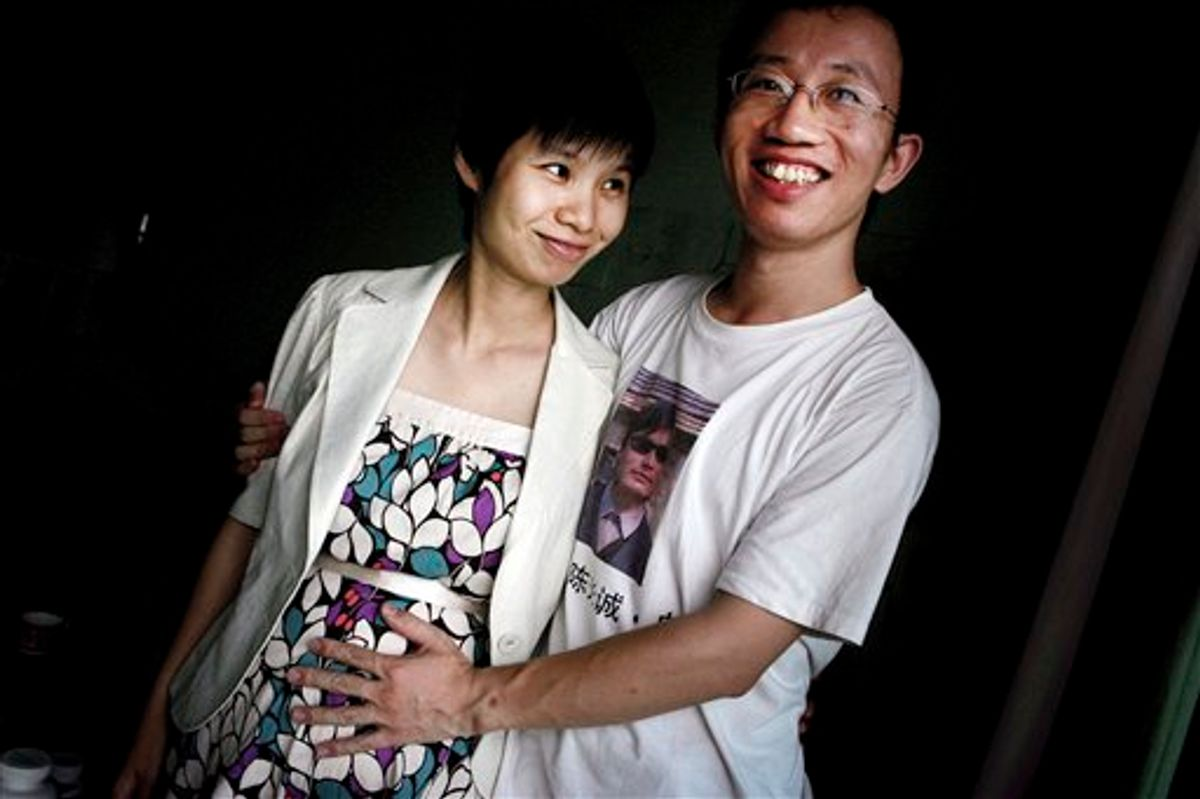 FILE - In this July 6, 2007 file photo, Hu Jia, right, and Zeng Jinyan, husband-and-wife activists, pose for a picture at their home in Beijing. Zeng said she visited Hu, who was jailed for sedition more than three years ago, in prison June 20, 2011. Jia was released Sunday, his wife said. (AP Photo/Elizabeth Dalziel, File) (AP)