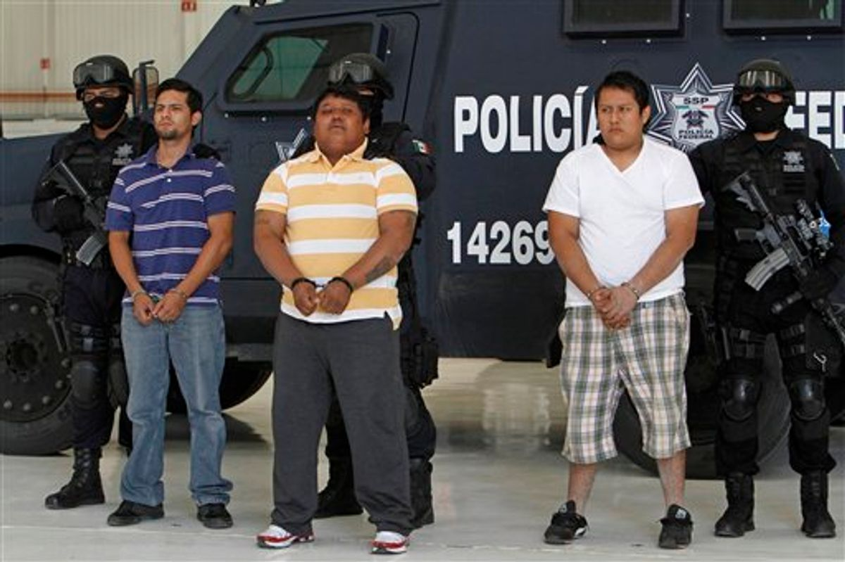 """Federal police officers escort Julio de Jesus Radilla Hernandez, aka """"El Negro"""", center, Jose Luis Luquin Delgado, aka """"El Jabon"""" , left, and  Valentin Ortiz Lopez, as they are presented to the press at the federal police headquarters in Mexico City, Wednesday, May 25, 2011. Mexico's federal police said Radilla Hernandez is allegedly responsible for ordering the March 27 murder of Juan Francisco Sicilia, son of Mexican poet Javier Sicilia and six other people. Luquin Delgado and Ortiz Lopez are also involved in the crime. (AP Photo/Marco Ugarte)  (AP)"""