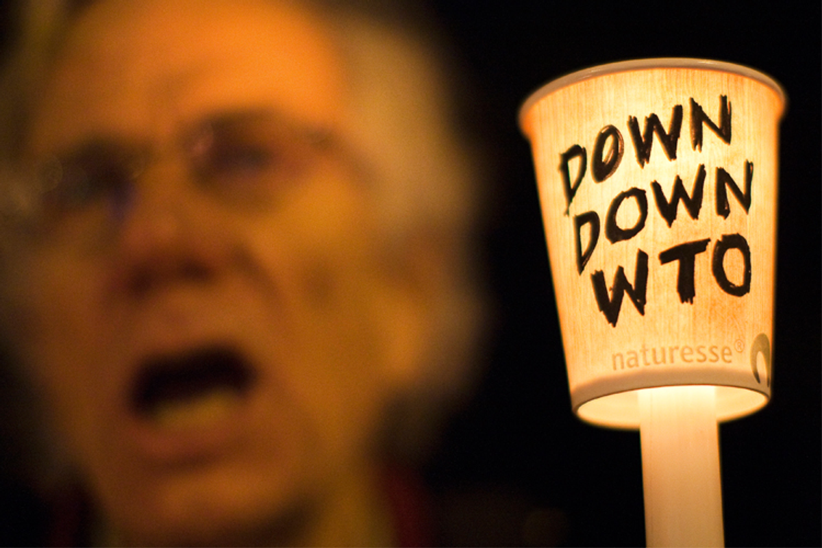 A protestor holds a candle during a demonstration against the WTO in Geneva on November 30, 2009