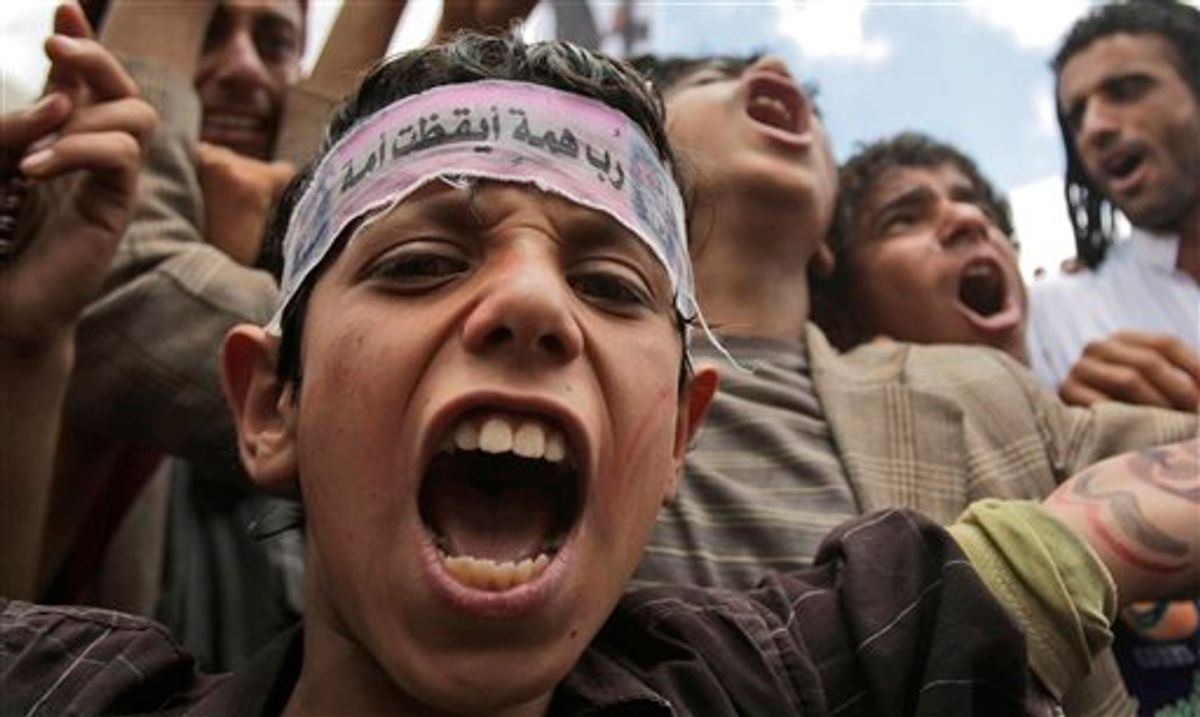 """A Yemeni boy, shouts slogans along with anti-government protestors during a demonstration demanding the resignation of Yemeni President Ali Abdullah Saleh, in Sanaa, Yemen, Thursday, June 2, 2011. Street battles raged Thursday between the army and opposition tribesmen in the capital Sanaa and dozens of people on both sides were killed and wounded. Elsewhere a thousands-strong force of tribal fighters fought to break through government lines on the northern outskirts of the city. Arabic reads on the boy's headband, """" Little efforts woke up a nation"""".  (AP Photo/Hani Mohammed) (AP)"""