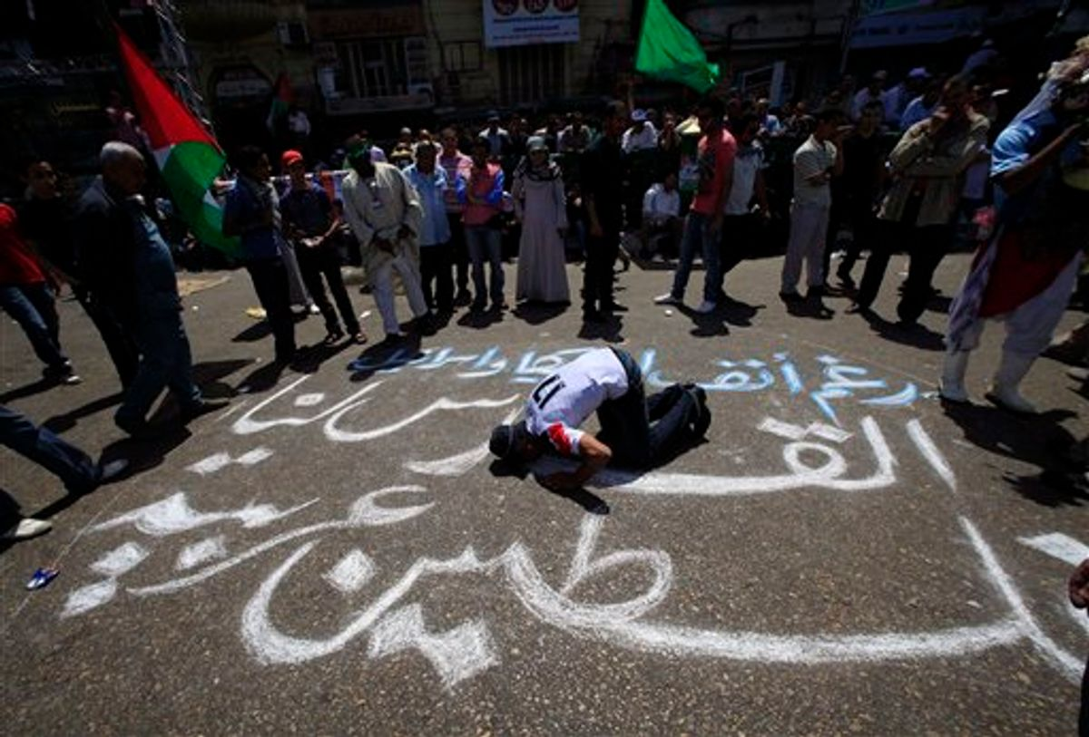 """An Egyptian prays on an Arabic slogan reads """" Jerusalem for us, Palestine is an Arabic land """" during a protest against Israel's closure of Gaza at Tahrir Square, the focal point of Egyptian uprising, in Cairo, Egypt Friday, May 13, 2011. (AP Photo/Amr Nabil) (AP)"""