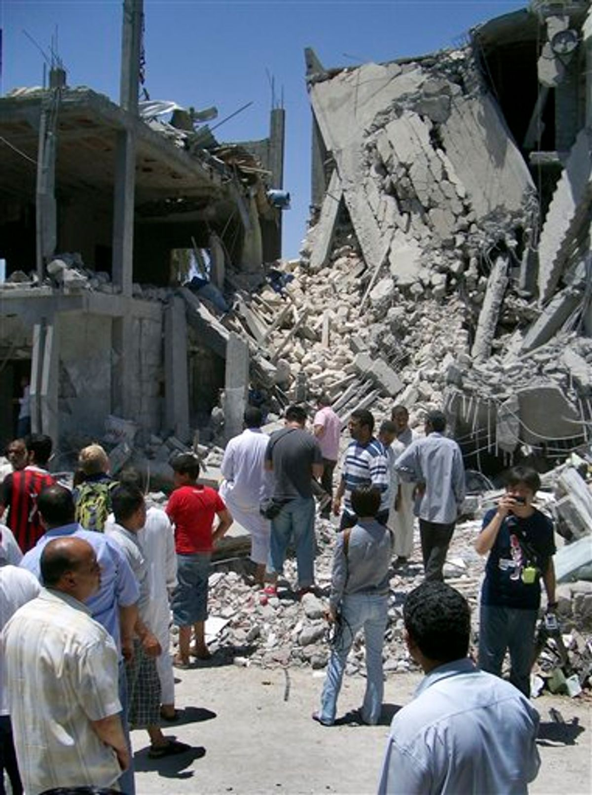 In this photo taken on a government-organized tour, media and others examine the remains of a damaged residential building in Tripoli, Libya, Sunday, June 19, 2011.  The Libyan government accused NATO of bombing a residential neighborhood in the capital and killing civilians early Sunday, adding to its charges that the alliance is striking non-military targets. (AP Photo/Adam Schreck) (AP)