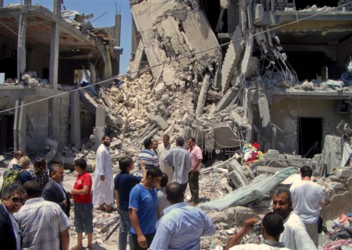 In this photo taken on a government-organized tour, members of the media and others examine the remains of a damaged residential building in Tripoli, Libya Sunday, June 19, 2011