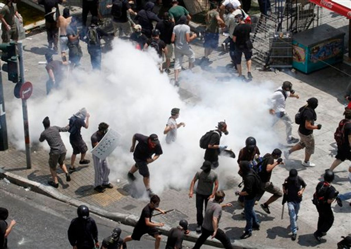 Demonstrators run away from tear gas  during a demo in Athens on Tuesday June 28, 2011. Greece's beleaguered government is bracing for a 48-hour general strike as lawmakers debate a new round of austerity reforms designed to win the country additional rescue loans needed avoid bankruptcy.(AP Photo/Dimitri Messinis)  (AP)