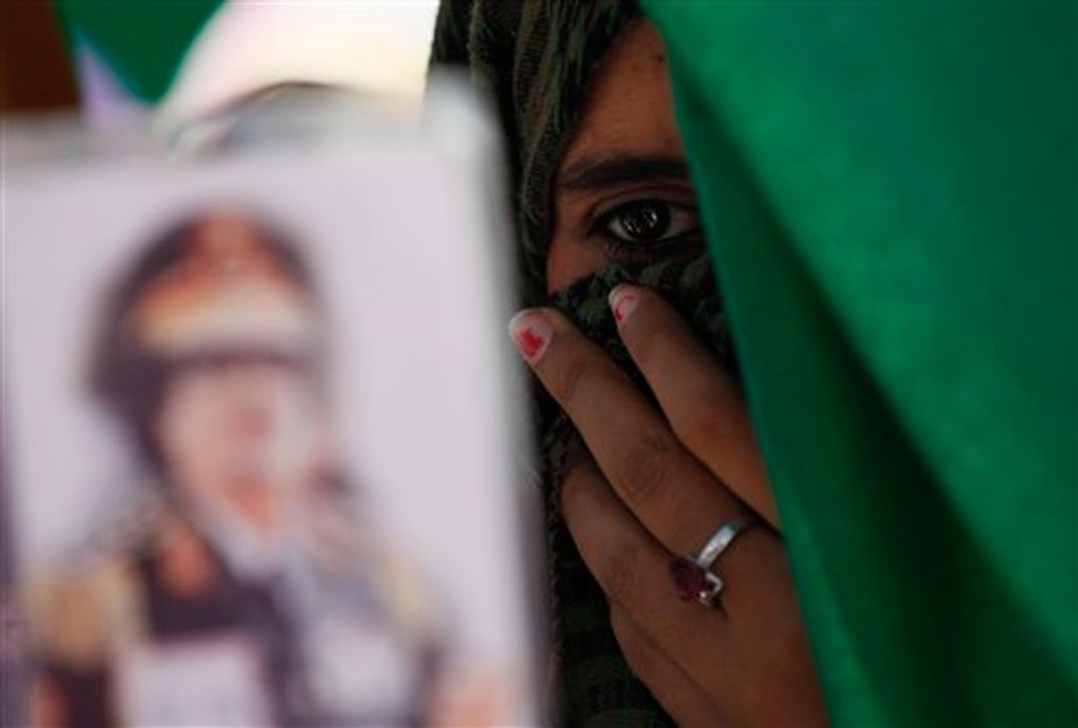 In this photo taken on a government-organized tourm a Libyan student holds a portrait of Libyan leader Moammar Gadhafi, outside the damaged university building in Tripoli, Libya, on Saturday, June 18, 2011. Libyan officials claim that one of the buildings at the university complex was recently hit by a NATO airstrike. (AP Photo/Ivan Sekretarev) (AP)