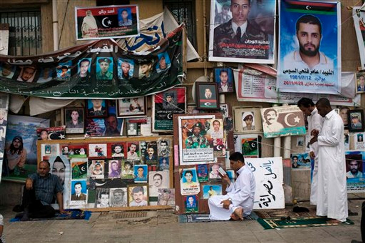 Men pray next to portraits of people killed or who disappeared during the rule of Libyan leader Moammar Gadhafi's regime during Friday prayers in Benghazi, Libya, June 3, 2011.  (AP Photo/Rodrigo Abd) (AP)