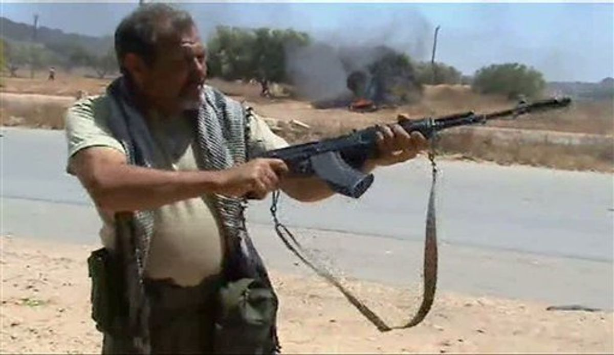 In this image taken from TV, showing rebel forces on the front line as they repel government troops, Sunday June 12, 2011, in Dafniya, Libya. as fighting continued on Sunday near Libya's main port of Misrata, a western redoubt of the rebels.  Video of the battle shows rebels advancing down a road, firing automatic weapons, guns mounted on pick up trucks, rockets and heavy artillery.  (AP Photo/APTN) TV OUT (AP)