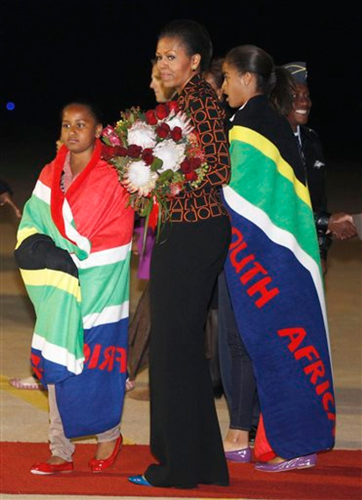 First lady Michelle Obama holds a bouquet of flowers, and daughters Malia, right, and Sasha, are draped in blankets given to them upon landing in Pretoria, en route to Johannesburg, South Africa, Monday, June 20, 2011, as they begin their week long trip to Africa. (AP Photo/Charles Dharapak, Pool)  (AP)