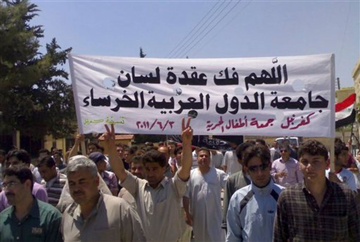 """In this citizen journalism image made on a mobile phone and provided by Shaam News Network, Syrian protesters hold an Arabic banner read:""""May God help break the silence of the Arab League,"""" as they march during a protest at the village of Kfar-Nebel, in the northen province of Edleb, Syria, on Friday June 3, 2011. Syrian troops pounded a central town with artillery and heavy machinegun fire Friday, killing at least two people in the latest onslaught as authorities cut off Internet service in several regions in an apparent move to prevent the uploading of videos of anti-regime demonstrations, activists said. (AP Photo/Shaam News Network) EDITORIAL USE ONLY, NO SALES, THE ASSOCIATED PRESS IS UNABLE TO INDEPENDENTLY VERIFY THE AUTHENTICITY, CONTENT, LOCATION OR DATE OF THIS HANDOUT PHOTO (AP)"""