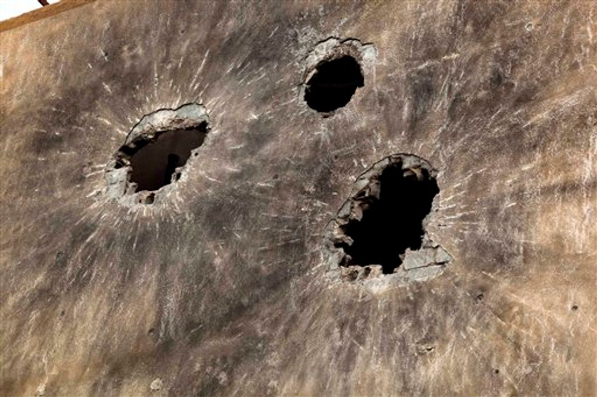 In this photo taken Sunday, May 22, 2011, holes caused by heavy ammunition are seen on the side wall of a building in Tripoli Street, the center of the fighting between forces loyal to Libyan-leader Moammar Gadhafi and rebels in downtown Misrata, Libya. Since the weeks-long siege of the city ended in mid-May, Misrata residents make pilgrimages to Tripoli Street, site of the fiercest fighting in the battle for Libya between the rebels and Moammar Gadhafi's forces. People gawk at the wreckage of bombed-out buildings with gaping holes and walls pocked by bullets, and shoot photos of charred hulks of tanks, rubble-strewn streets and a side walk museum featuring drumloads of bullet casings, uniforms of dead enemies, and unexploded munitions. (AP Photo/Rodrigo Abd) (AP)
