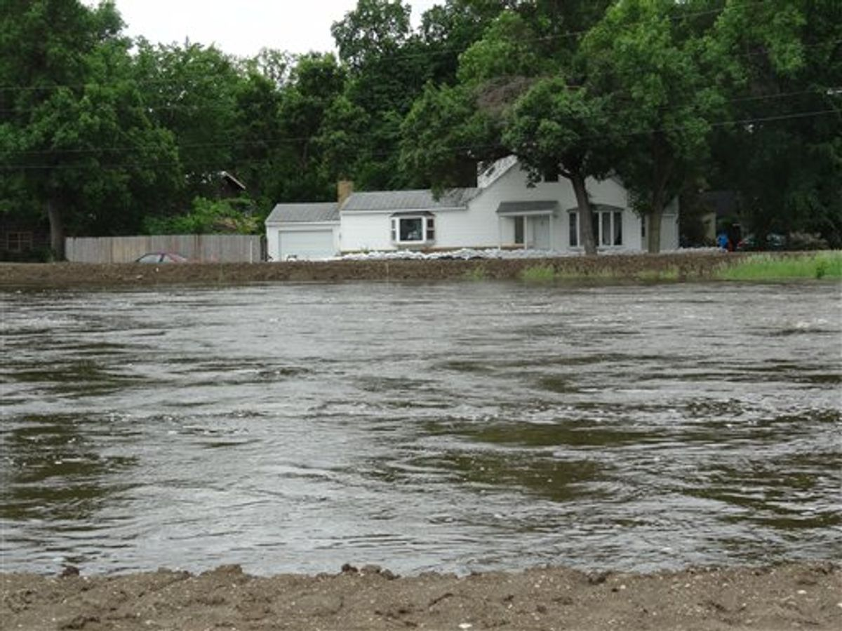 The Souris River passes near a home Tuesday, June 21, 2011, in Minot, N.D. About 11,000 Minot residents are being ordered to leave their homes even earlier than expected this week as the river gets closer to swamping the North Dakota city with the worst flooding in four decades, officials said Tuesday. (AP Photo/ The Forum, Teri Finneman) (AP)