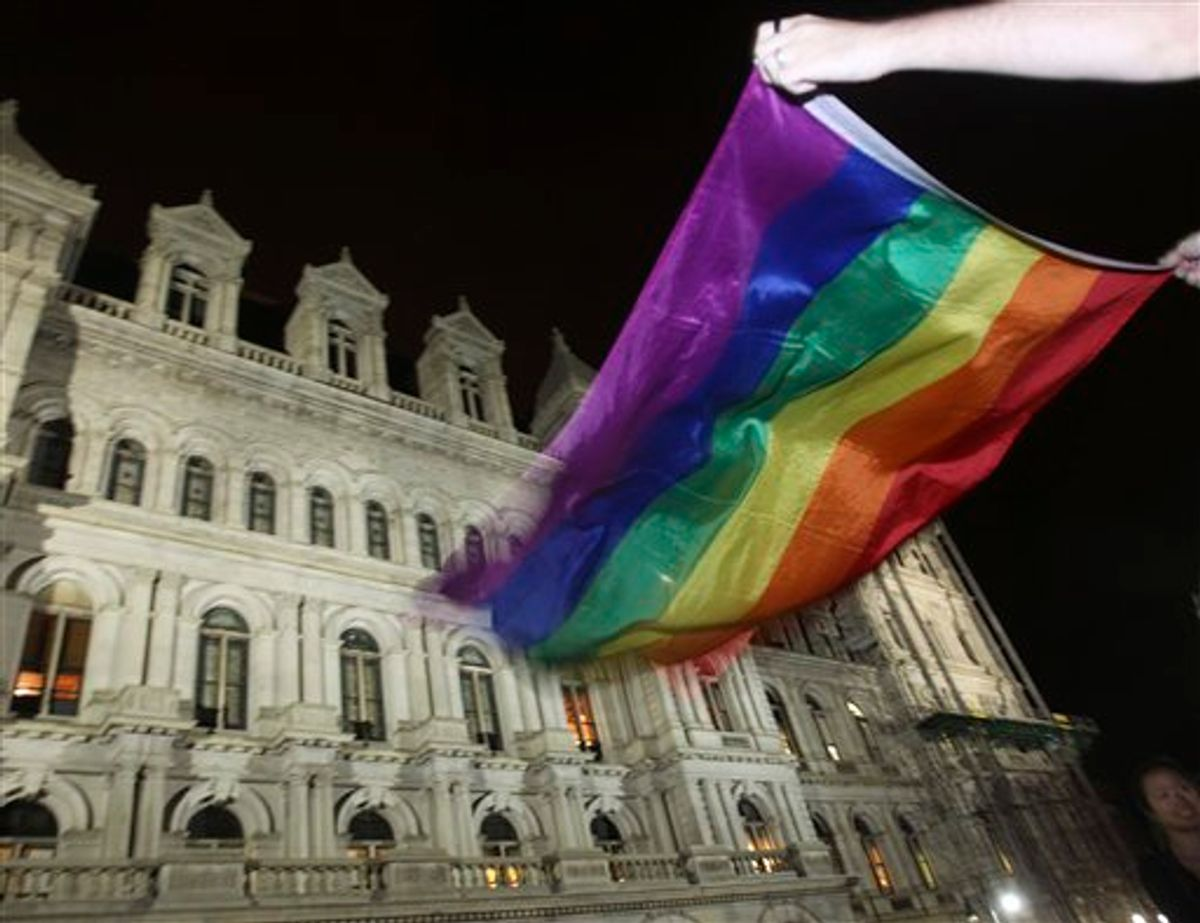 Robert Moore of New York waves a Pride flag outside the Capitol in Albany, N.Y., after the state Senate passed a bill legalizing same-sex marriage, on Friday, June 24, 2011.  (AP Photo/Mike Groll) (AP)