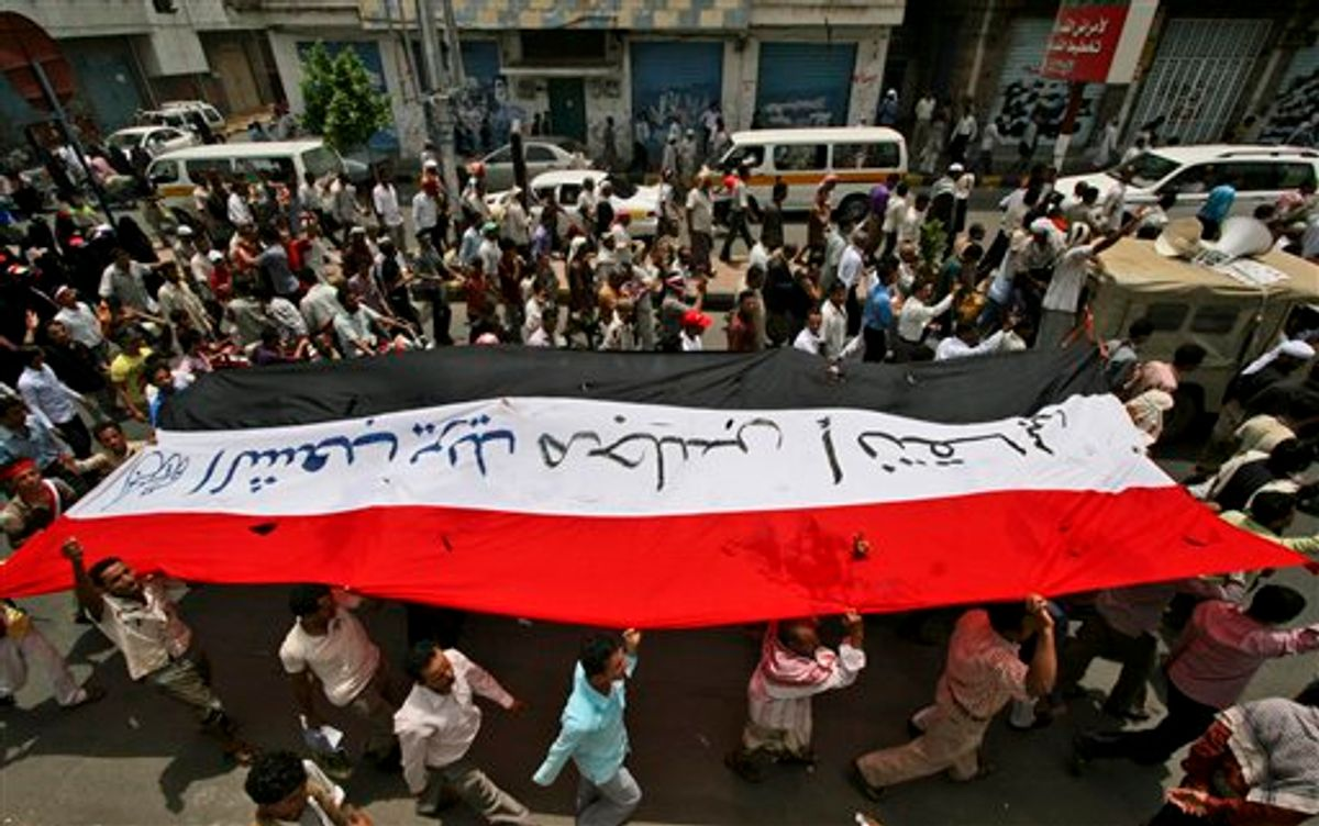 """Anti-government protestors hold up their national flag, bearing the words """"The people want a transitional council"""" in Arabic, during a demonstration demanding the resignation of Yemeni President Ali Abdullah Saleh, in Taiz, Yemen, Monday, June 20, 2011. Tens of thousands of Yemenis have taken to the streets of the capital, demanding that the president's son leave the country. Ahmed Saleh, 42, is a one-time heir apparent who commands the elite Yemeni Presidential Guard. The force has been leading the crackdown on pro-democracy demonstrators since the uprising began in February. (AP Photo/Anees Mahyoub) (AP)"""