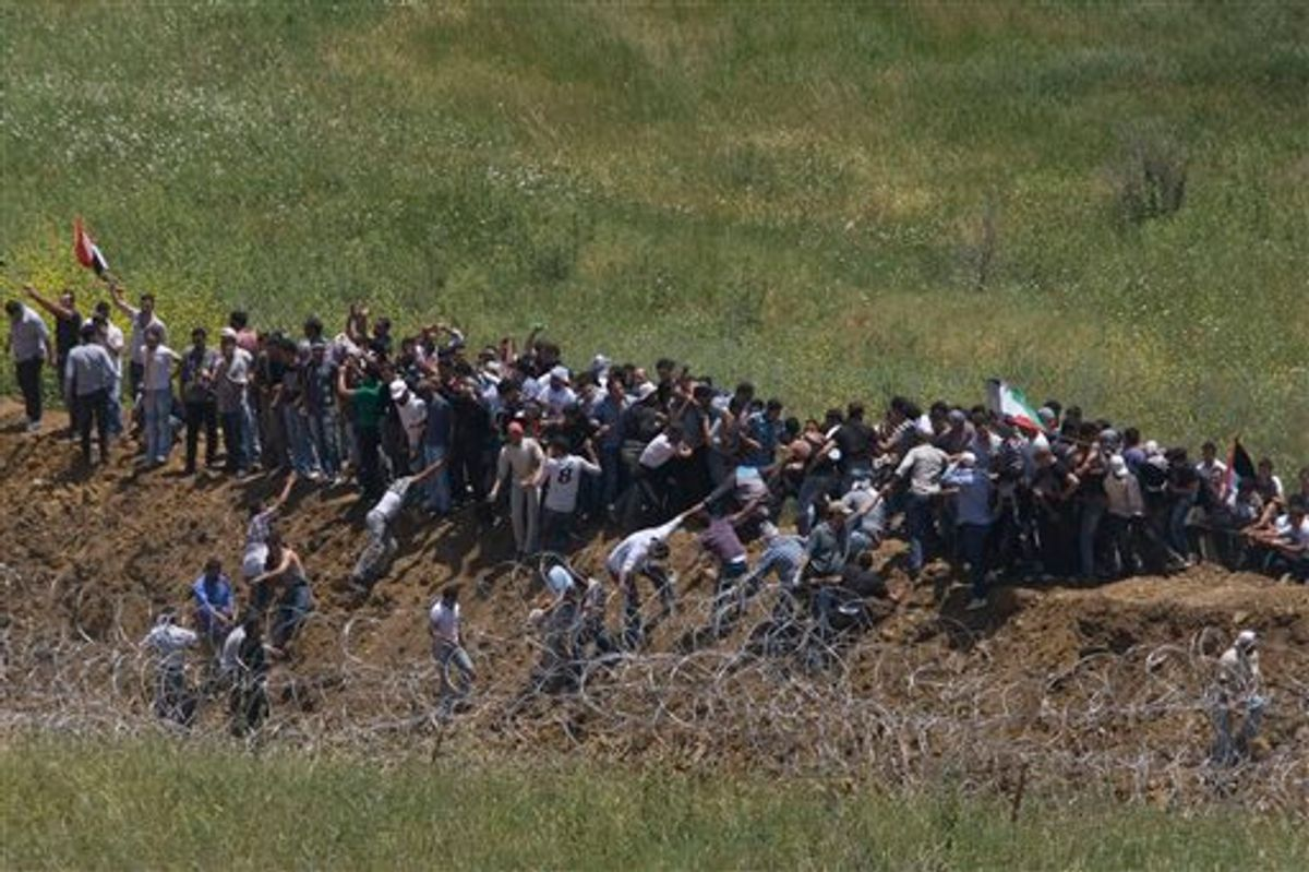 Pro Palestinians protesters try to break a fence along the border between Israel and Syria near the village of Majdal Shams in the Golan Heights, Sunday, June 5, 2011 . Israeli troops opened fire across the Syrian frontier on Sunday to disperse hundreds of pro-Palestinian protesters who stormed the border of the Israeli-controlled Golan Heights, reportedly killing four people in unrest marking the anniversary of the Arab defeat in the 1967 Mideast war. (AP Photo/Ariel Schalit) (AP)