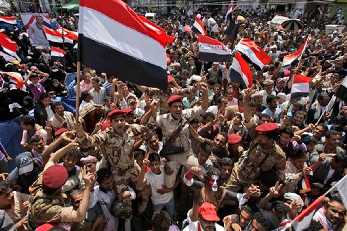 Yemeni army soldiers lifted by anti-government protestors, chants slogans and wave their national flag as they celebrate President Ali Abdullah Saleh's departure to Saudi Arabia, in Sanaa, Yemen, Sunday, June 5, 2011. Thousands of protesters are dancing and singing in the Yemeni capital Sanaa after the country's authoritarian leader flew to Saudi Arabia to receive medical treatment for wounds he suffered in a rocket attack on his compound. (AP Photo/Hani Mohammed) (AP)