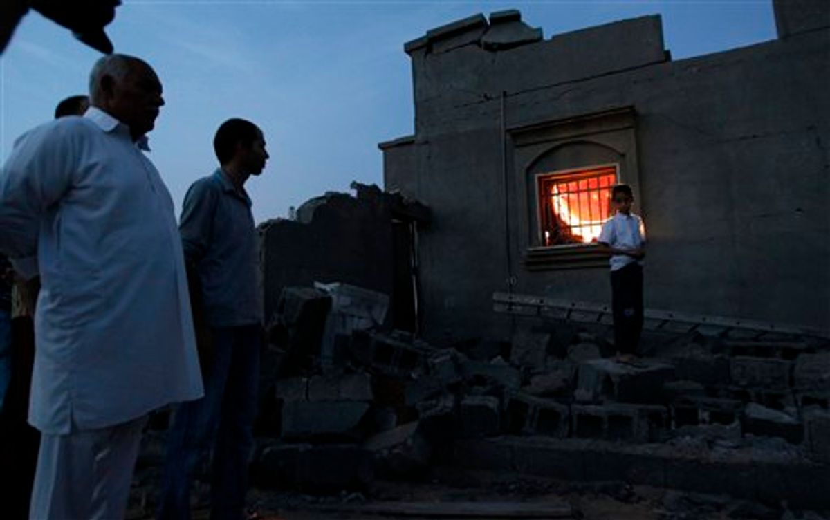 In this photo taken on a government organized tour, local residents stand next to a damaged house in Tripoli, Libya, on Sunday, June 5, 2011. Libyan officials claim that during a NATO airstrike, a rocket targeted a nearby military site hit a residential area and damaged several houses. (AP Photo/Ivan Sekretarev) (AP)