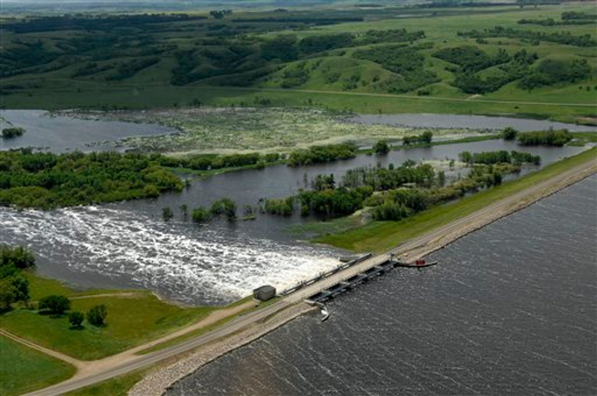 Water flows from Lake Darling into the Souris River on Wednesday, June 22, 2011. Lake Darling is located about fifteen miles north of Minot, ND.  As many as 10,000 people raced to evacuate Wednesday as water began spilling over Minot's levees. The river, which begins in the Canadian province of Saskatchewan and flows for a short distance though North Dakota, was all but certain to inundate thousands of homes and businesses during the next week. (AP Photo/Will Kincaid) (AP)