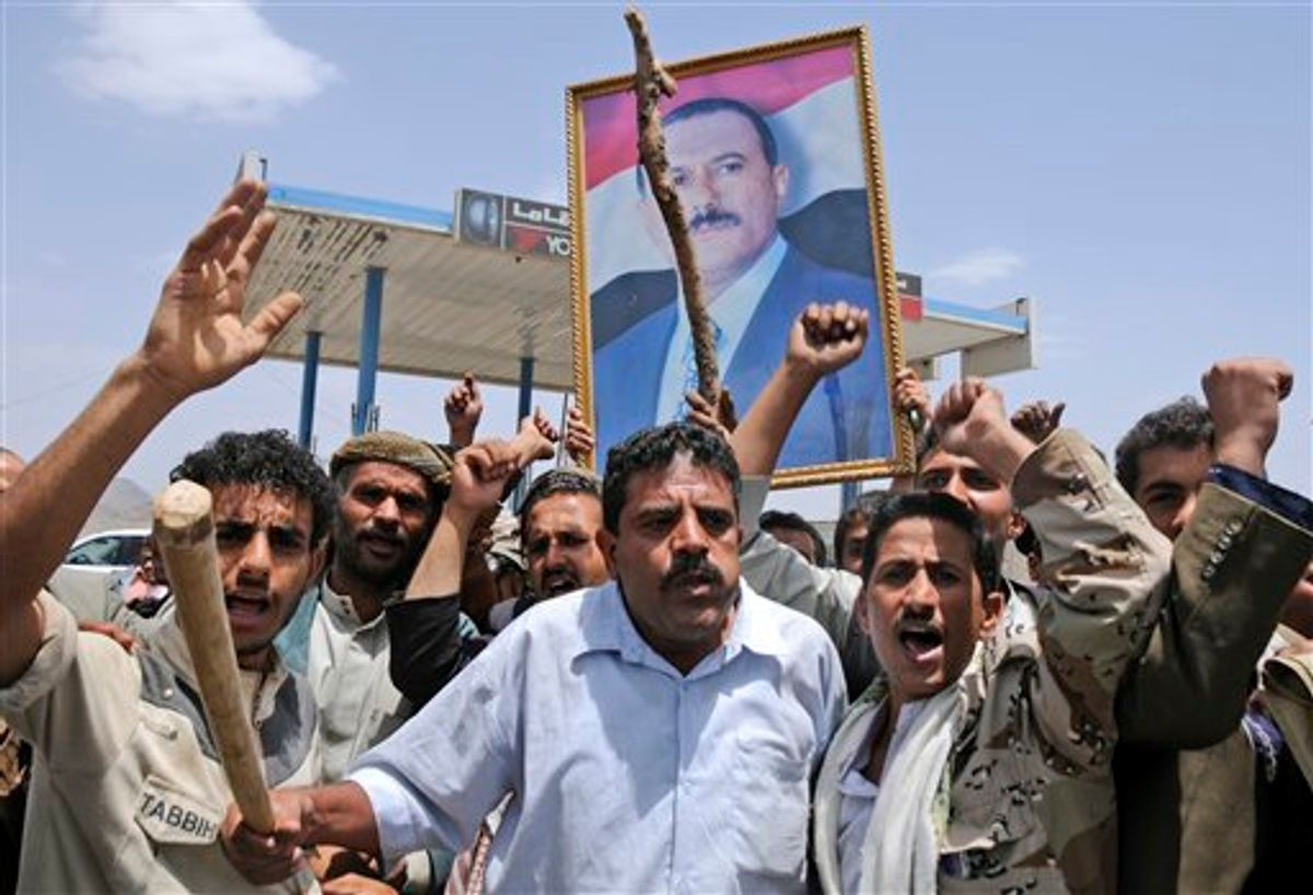 Supporters of Yemeni President Ali Abdullah Saleh hold up his portrait and chant slogans as they celebrate news that Saleh's health is stable, after being taken to Saudi Arabia to receive medical treatment for wounds he suffered in a rocket attack on his compound, in Sanaa, Yemen, Thursday, June 9, 2011. Government troops trying to recapture areas held by Islamic militants have killed 12 suspected al-Qaida members in the troubled southern province of Abyan, the Defense Ministry said Thursday. (AP Photo/Mohammed Al-Sayaghi) (AP)