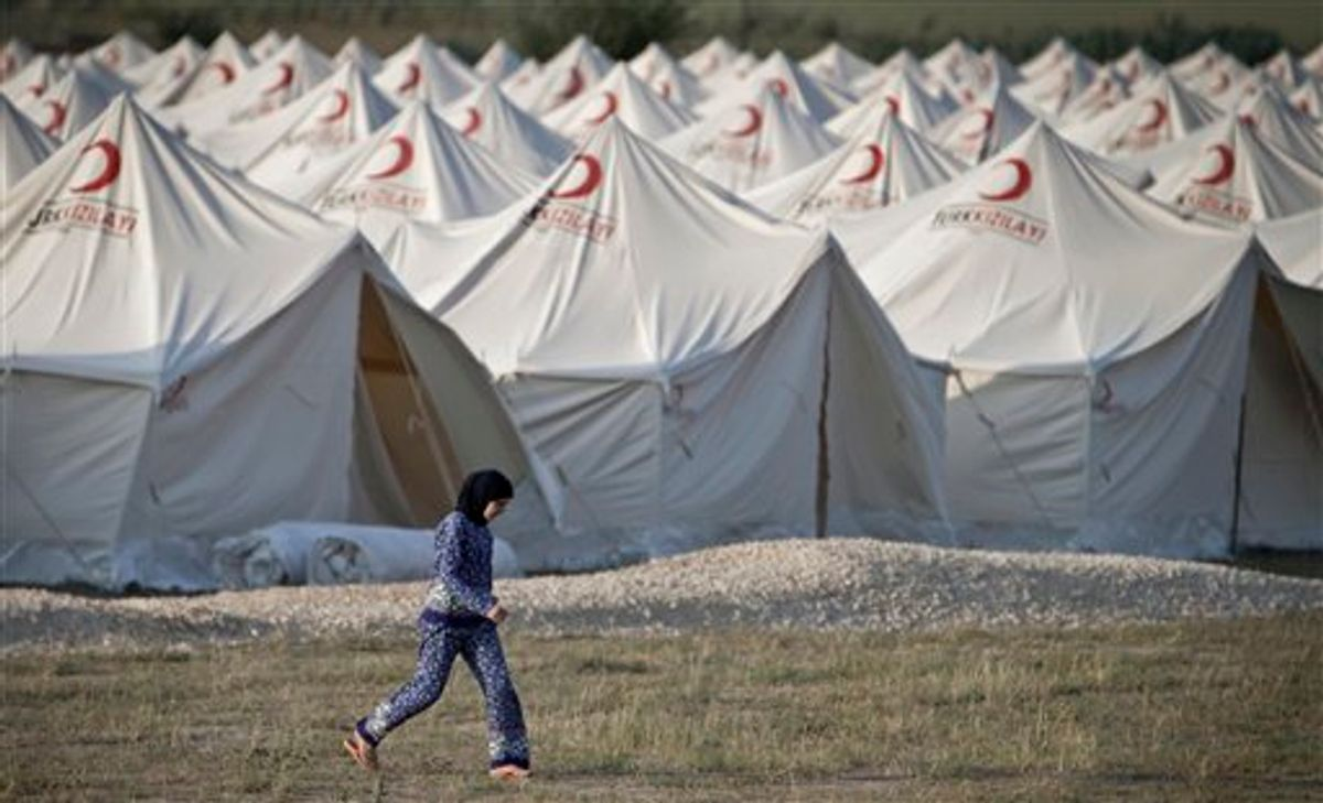 A Syrian refugee woman walks in the new refugee tent compound in Boynuyogun, Turkey, near the Syrian border, Sunday, June 12, 2011. Syrian forces launched a crackdown on the Syrian town of Jisr al-Shughour on Sunday, fueling fears that the clashes could spark a further influx of refugees towards bordering Turkey.(AP Photo/Vadim Ghirda) (AP)