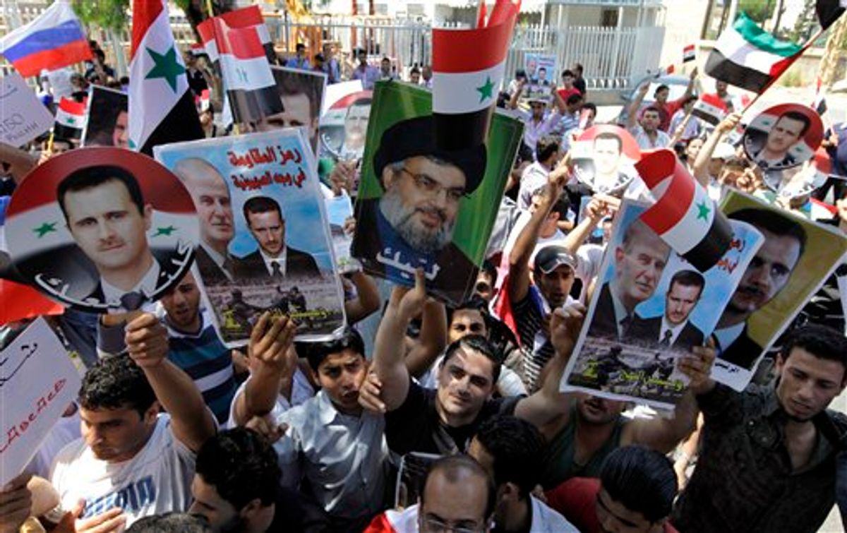 Protesters shout slogans as they carry pictures of Syrian President Bashar Assad, left, his father Hafez Assad, second from left, Hezbollah leader Sheik Hassan Nasrallah, center, and Syrian flags, during a demonstration to show their support for the Syrian President in front of the Russian Embassy, in Beirut, Lebanon, Sunday, June 19, 2011. (AP Photo/Bilal Hussein) (AP)