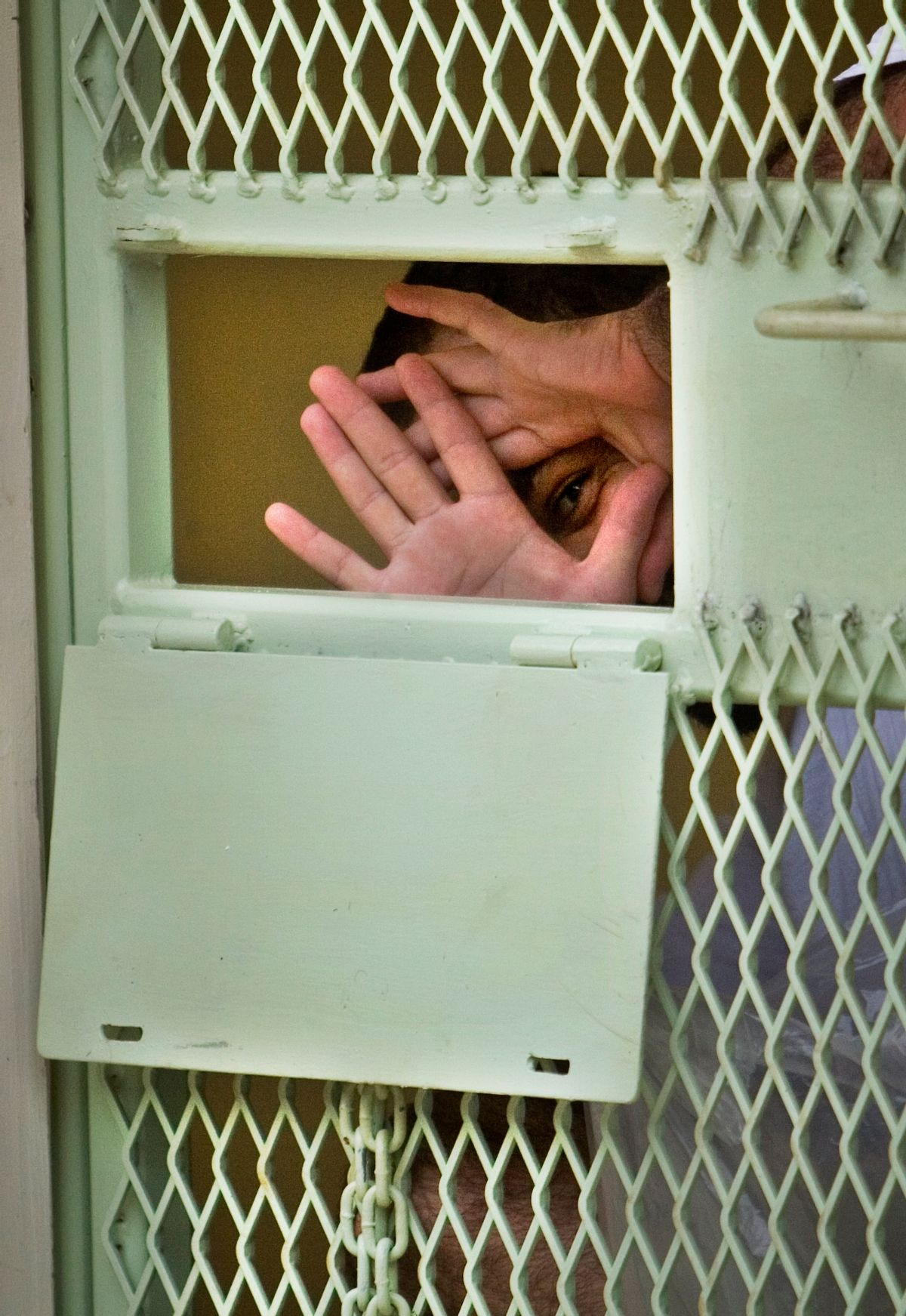 **FILE** In this Nov. 18, 2008 file photo, reviewed by the U.S. Military, a Guantanamo detainee peers through his hands from inside his cell at the Camp Echo detention facility at the U.S. Naval Base, in Guantanamo Bay, Cuba. A U.S. appeals court has overturned a ruling, Wednesday, Feb. 18, 2009, that would have transferred 17 Guantanamo Bay detainees to the United States. The men have been cleared for release from Guantanamo, but the United States will not send them home to China for fear they will be tortured. So they remain in prison while the U.S. figures out what to do with them. (AP Photo/Brennan Linsley, File) (Associated Press)