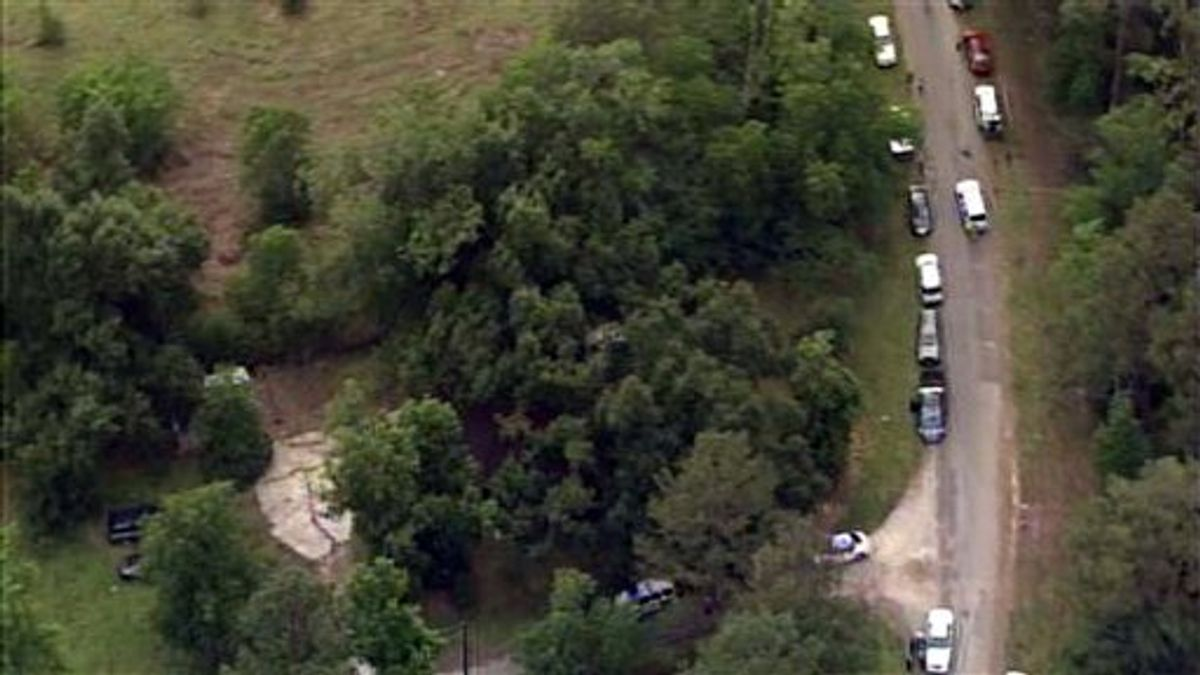This image provided by KPRC-TV shows authorities at a rural house after receiving a tip that multiple dismembered bodies are buried there, in Liberty County, Texas, Tuesday, June 7, 2011. (AP Photo/KPRC-TV) MANDATORY CREDIT (AP)