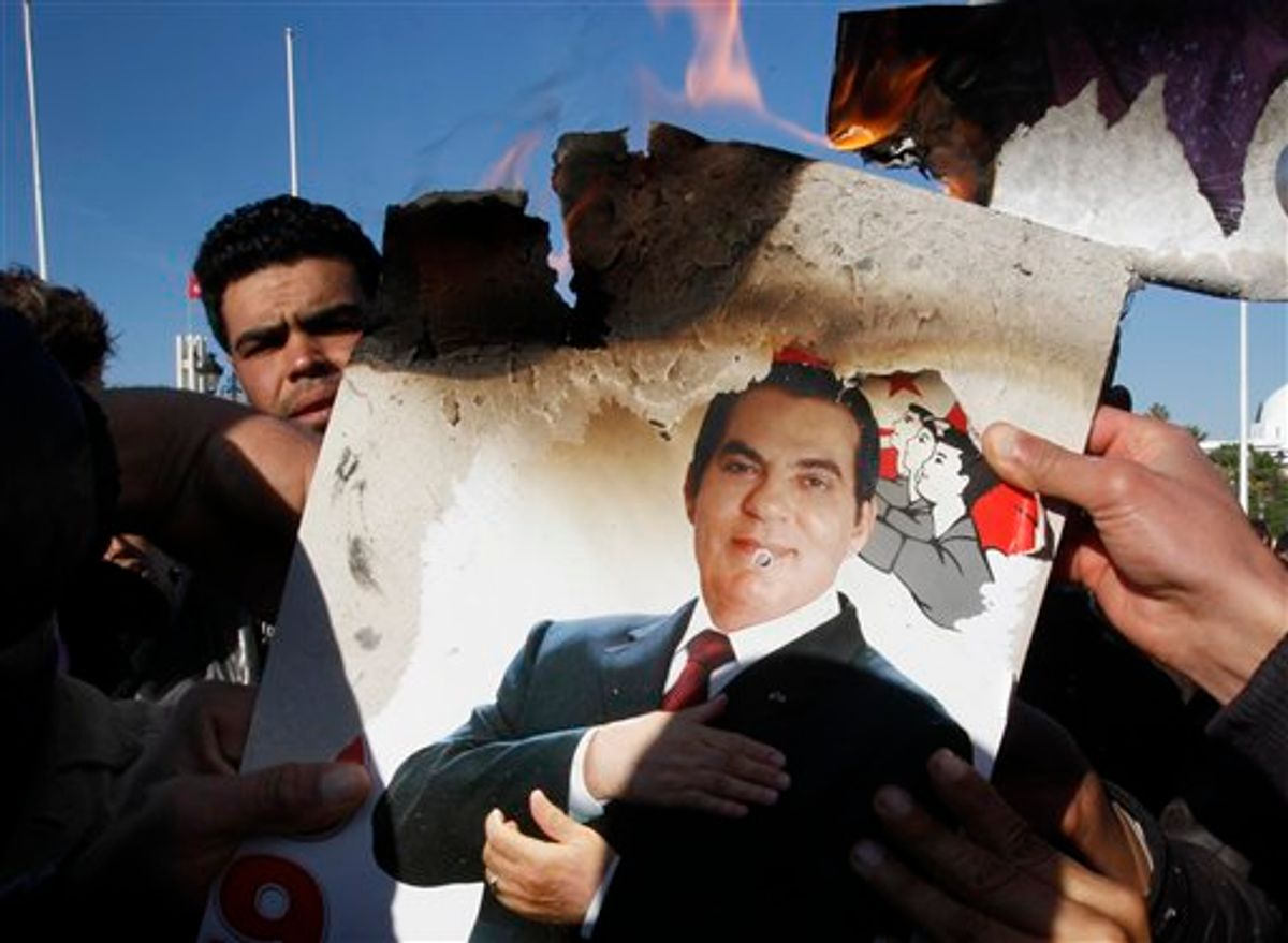 """FILE - In this Monday, Jan. 24, 2011 picture, protestors burn a photo of former Tunisian President Zine El Abidine Ben Ali during a demonstration against holdovers from Ben Ali's regime in the interim government in Tunis, Tunisia. Tunisia's former autocratic leader whose downfall triggered uprisings in the Arab world has condemned his upcoming trial in absentia in Tunis as a """"shameful masquerade."""" Ben Ali - in exile in Saudi Arabia - also said Sunday, June 19, 2011 in a statement from his French lawyer that he didn't flBeee Tunisia but left to avoid """"fratricidal and deadly confrontations."""" (AP Photo/Christophe Ena, File) (AP)"""