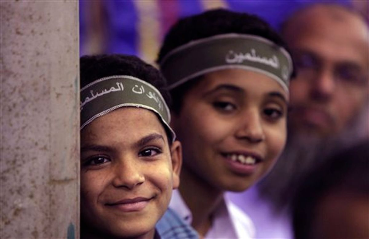 """In this Wednesday, May 18, 2011 picture, two Egyptian boys wear headbands reading """"Muslim Brotherhood"""" as they and other supporters attend a Muslim Brotherhood electoral rally in the Munib neighborhood of Cairo, Egypt. Once forced underground, the Brotherhood is likely to be part of Egypt's new government, fueling fears of Islamic rule. But the Brotherhood's own identity is on the line, and there is pressure from inside and out for it not to go down a sharp-right Islamic road. (AP Photo/Nasser Nasser) (AP)"""