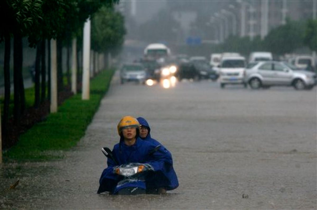 Two men on a motorcycle are stuck in floodwaters in Wuhan in central China's Hubei province Saturday June 18, 2011. Flooding from this month's seasonal rains has already forced hundreds of thousands of people from their homes and left more than 170 dead or missing. (AP Photo) CHINA OUT (AP)