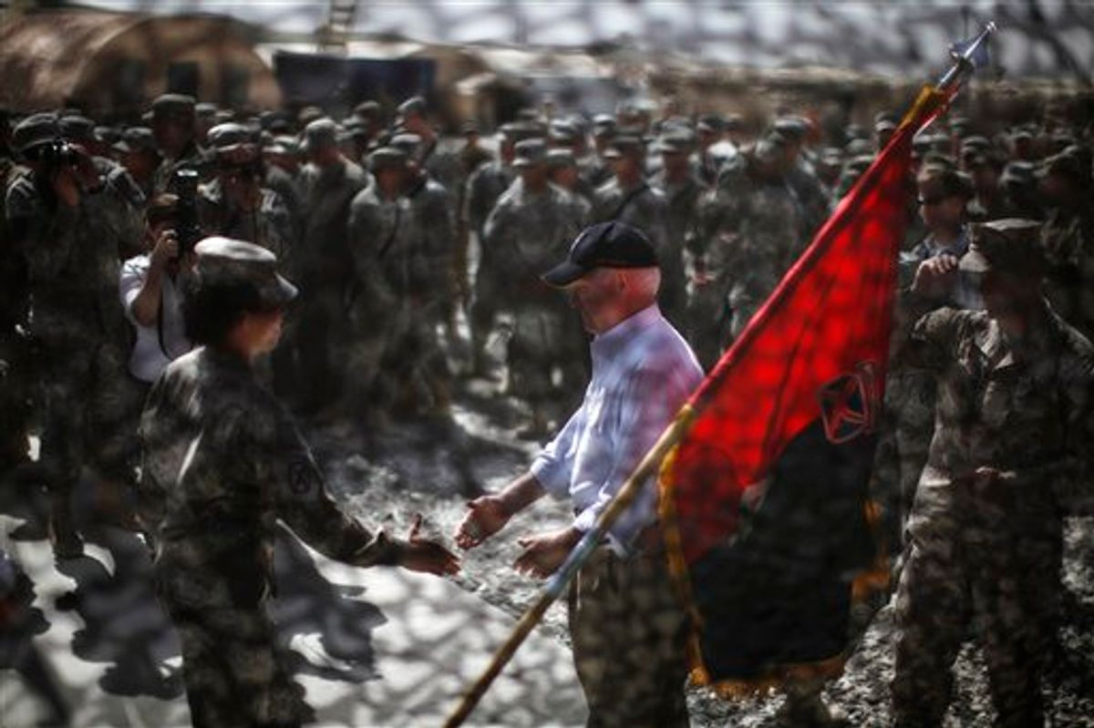 Defense Secretary Robert Gates is seen through camouflage netting as he greets US. Army soldiers at Forward Operating Base (FOB) Shank in Logar Province, Afghanistan, Monday, June 6, 2011.    (AP Photo/Jason Reed, Pool) (AP)