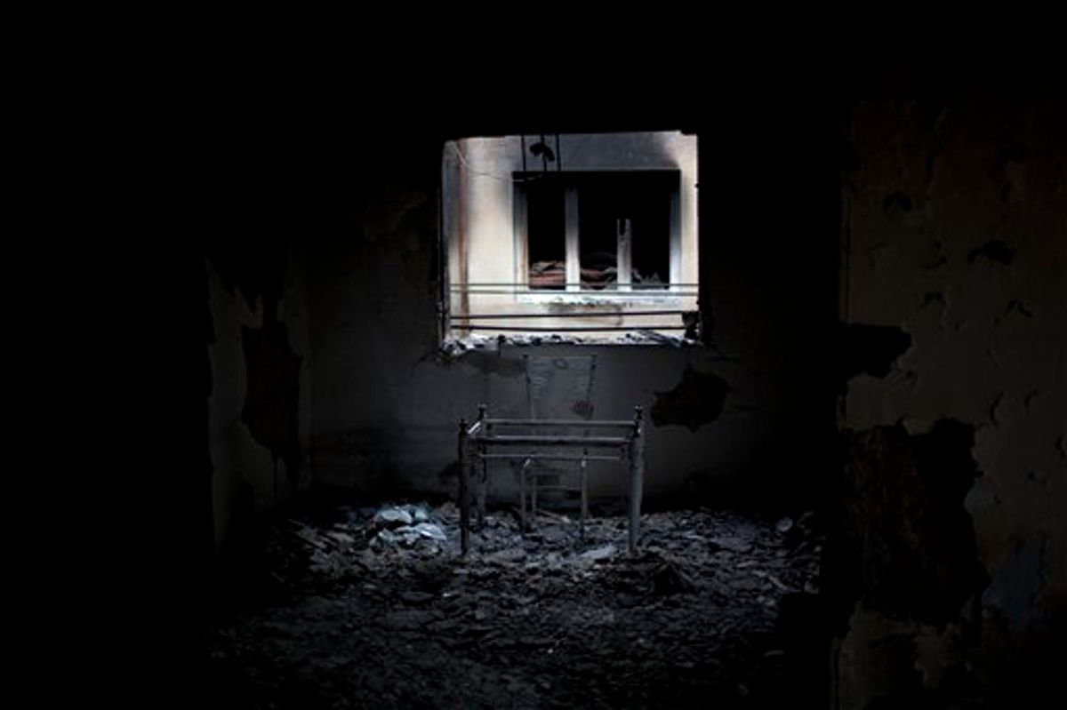 In this photo taken Tuesday, May 24 , 2011, a table and a chair are seen in an apartment used by snipers loyal to Libyan-leader Moammar Gadhafi and destroyed during fighting with rebels for the control of Tripoli Street, Misrata, Libya. Since the weeks-long siege of the city ended in mid-May, Misrata residents make pilgrimages to Tripoli Street, site of the fiercest fighting in the battle for Libya between the rebels and Moammar Gadhafi's forces. People gawk at the wreckage of bombed-out buildings with gaping holes and walls pocked by bullets, and shoot photos of charred hulks of tanks, rubble-strewn streets and a side walk museum featuring drumloads of bullet casings, uniforms of dead enemies, and unexploded munitions. (AP Photo/Rodrigo Abd) (AP)